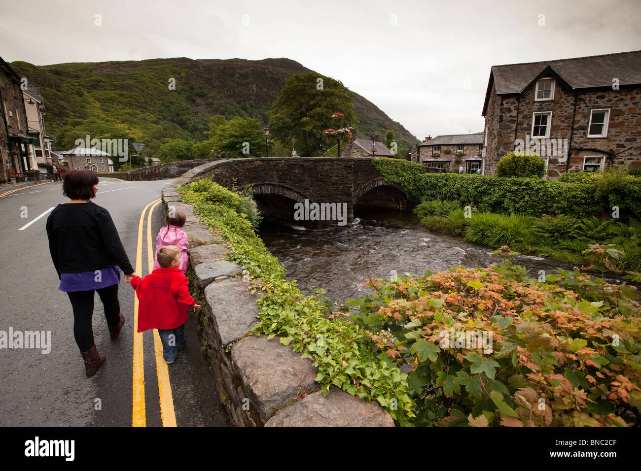 UK, Wales, Snowdonia, Beddgelert, young family walking in road at old stone bridge over Afon Colwyn - Stock Image