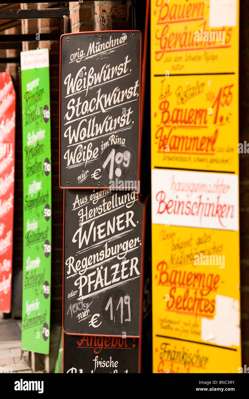 Signs advertise various types of German sausage and meat products at the Viktualienmarkt in Munich, Bavaria, Germany. - Stock Image