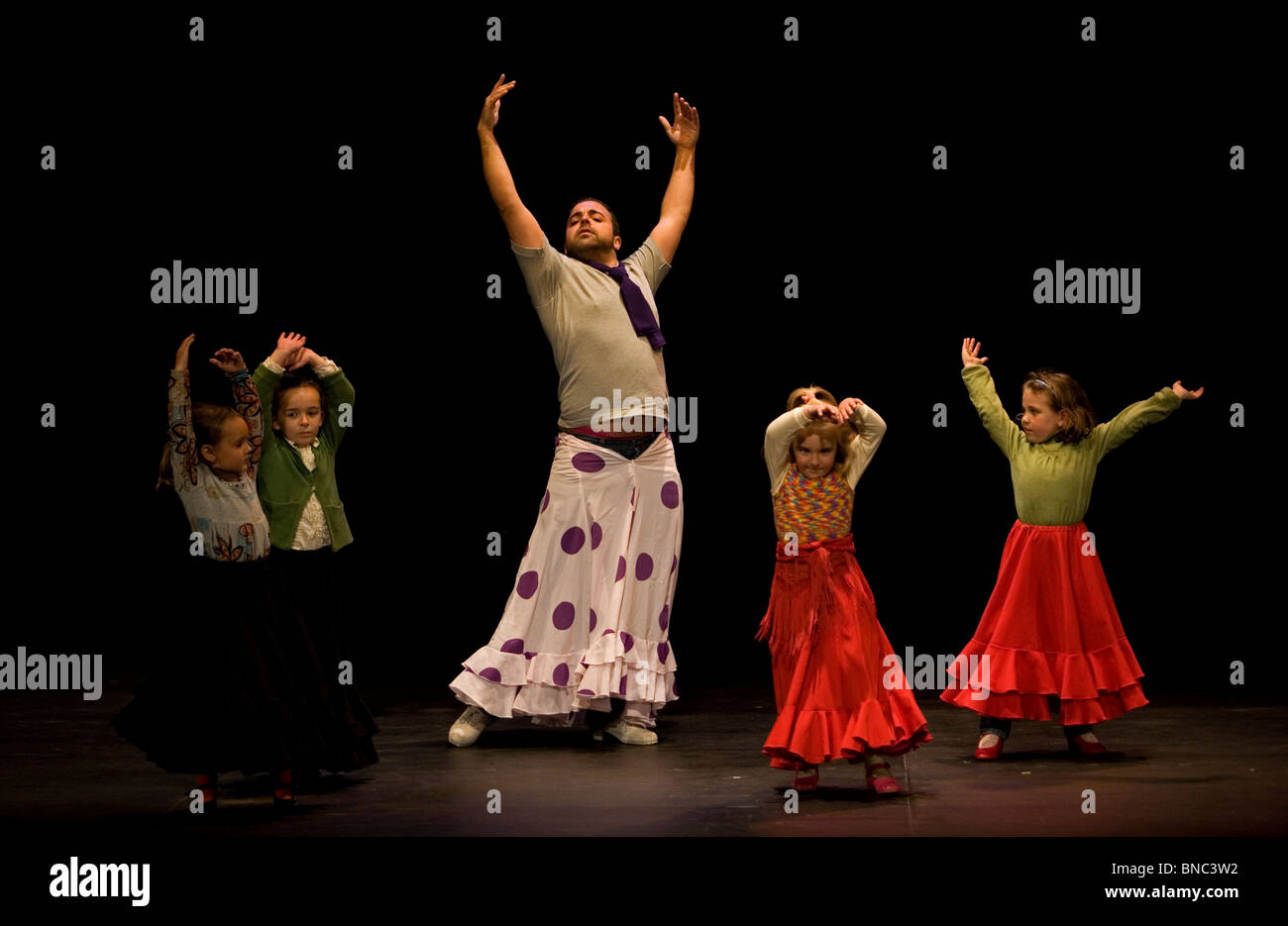 A Flamenco dancer, or bailaor, wears a polka-dot skirt to help him teach young girls to dance in Prado del Rey, - Stock Image
