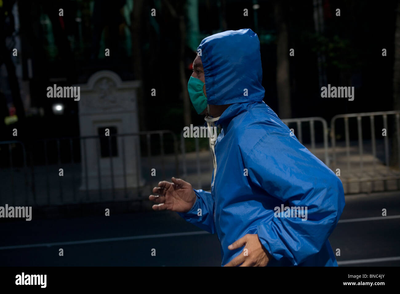 An man wears a surgical mask as a precaution against pollution as he jogs in Mexico City, December 13, 2009. - Stock Image