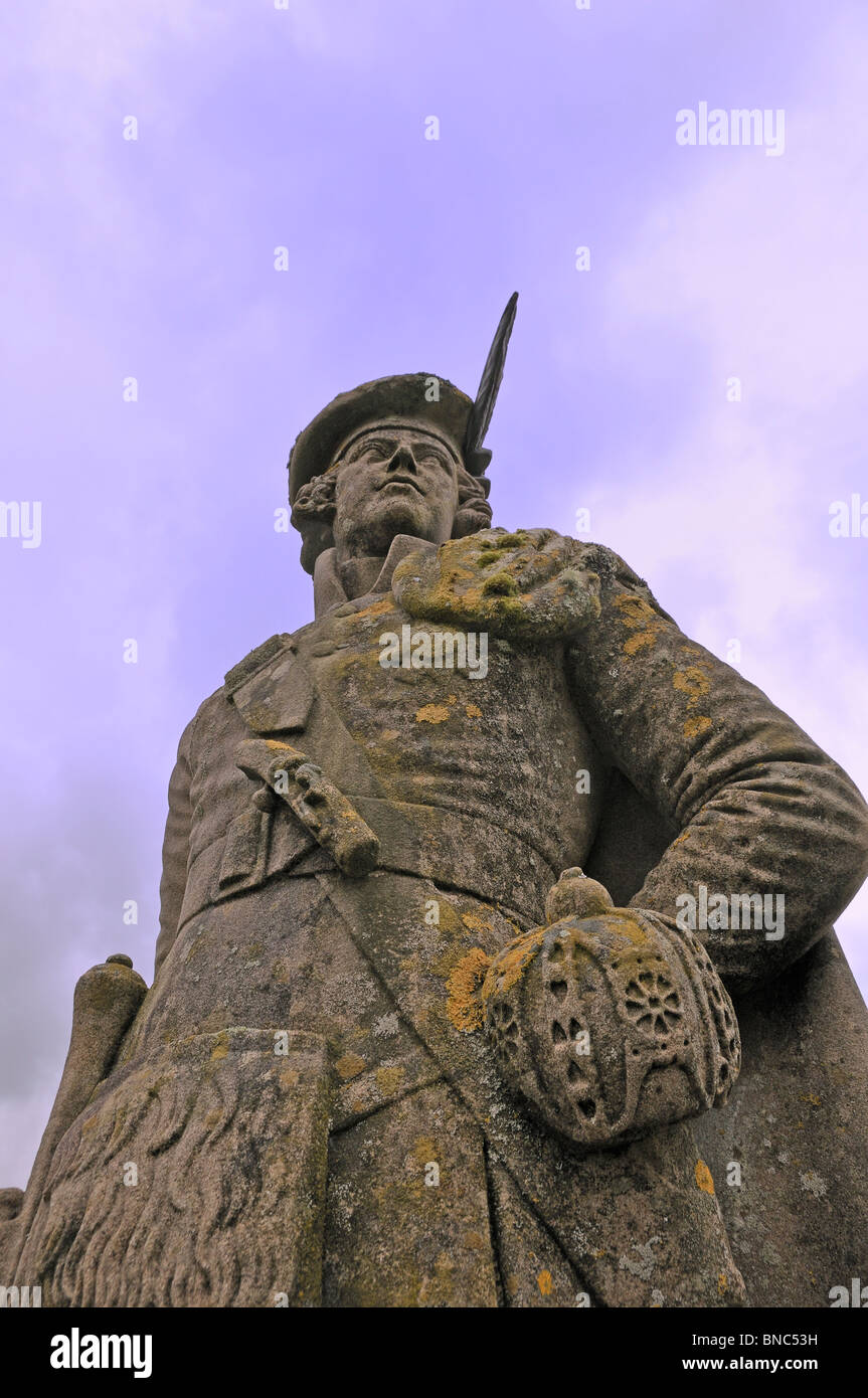 Adorned by lichens, the unkown highlander statue stands tall atop the Glenfinnan monument - Stock Image