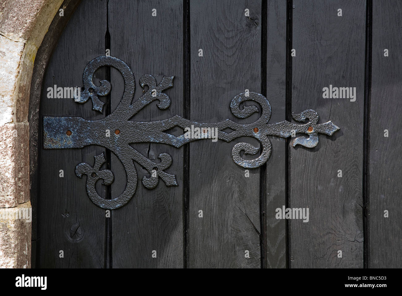 Old dark wooden door with elaborate iron hinge - Stock Image