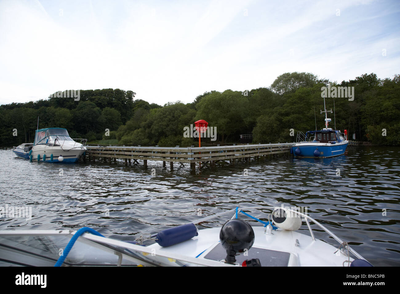 small boat approaching public jetty on rams island in lough neagh northern ireland uk - Stock Image