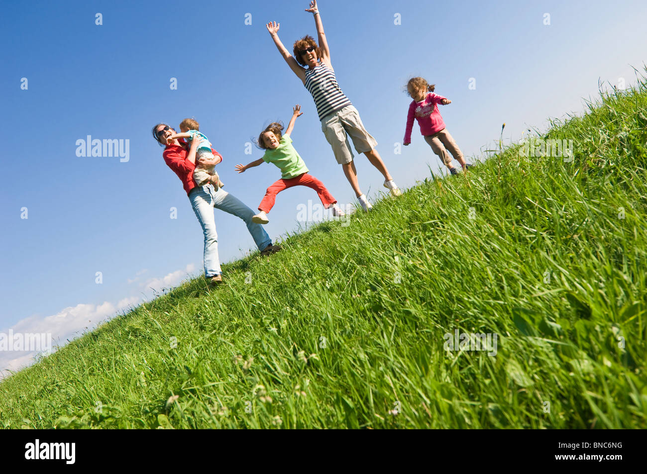 Family playing with joy on a grassy hill in Trentino, Italy. Stock Photo