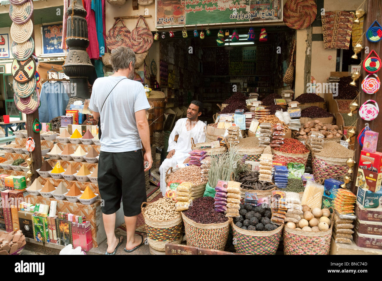 A tourist shopping for spices in the market, Aswan, Upper Egypt - Stock Image