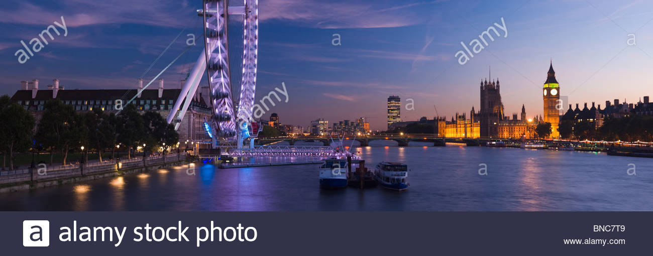 Panoramic view of the London Eye and The Houses of Parliament at night, London, UK. Stock Photo