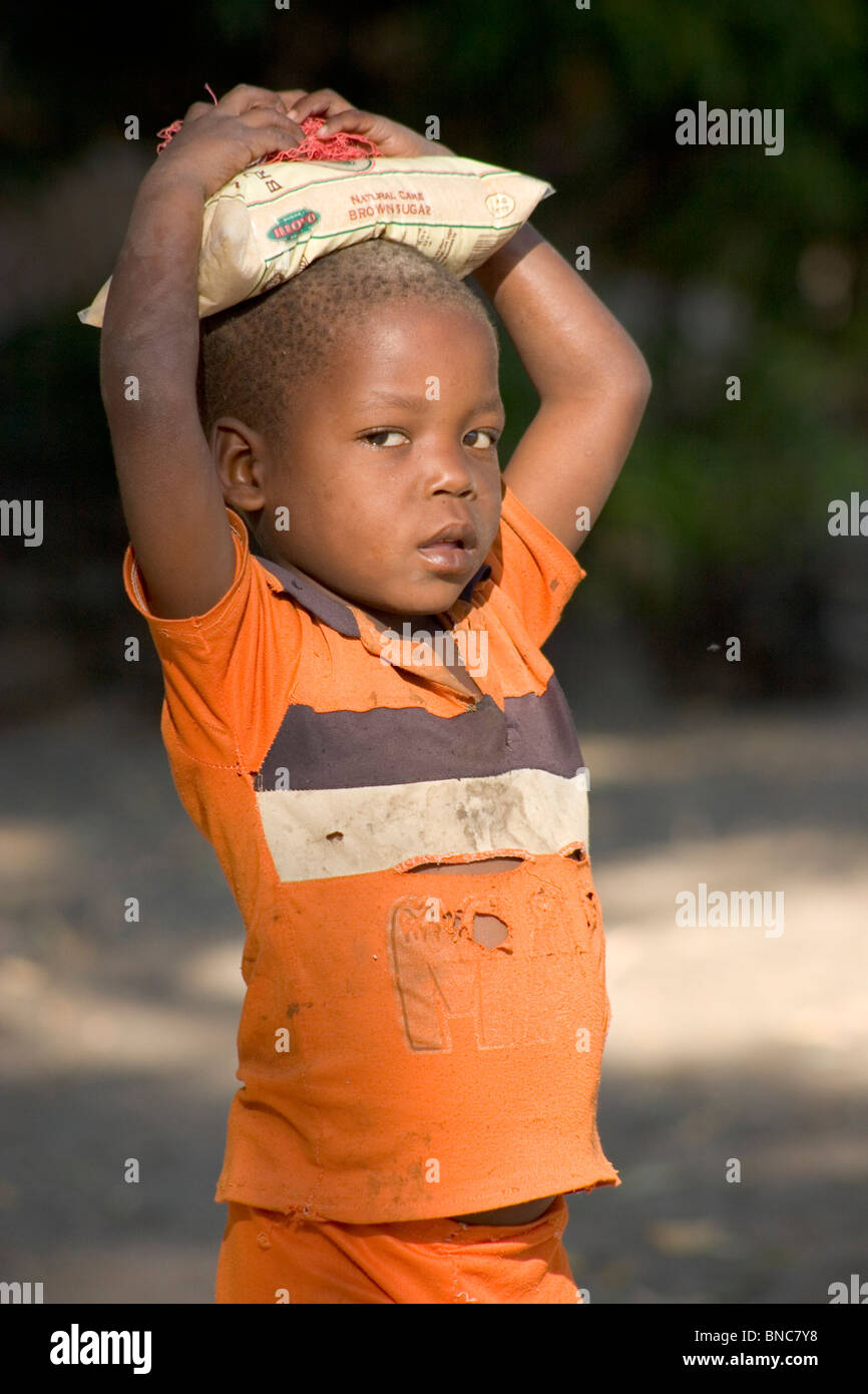 Malawian boy carrying bag of sugar on his head, Chizumulu Island. - Stock Image