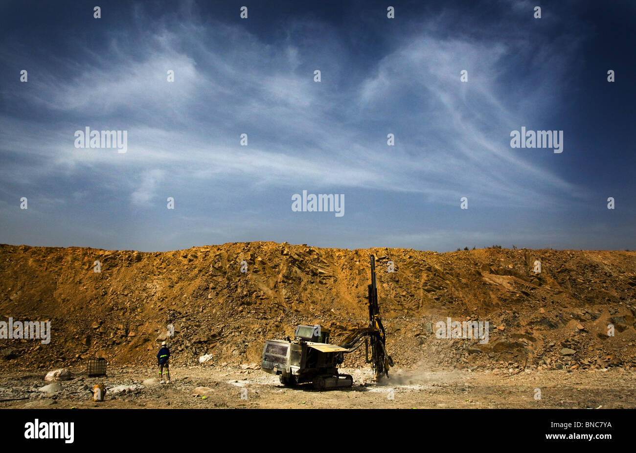 A worker watches over a mining drill in the main pit of the Youga gold mine - Stock Image