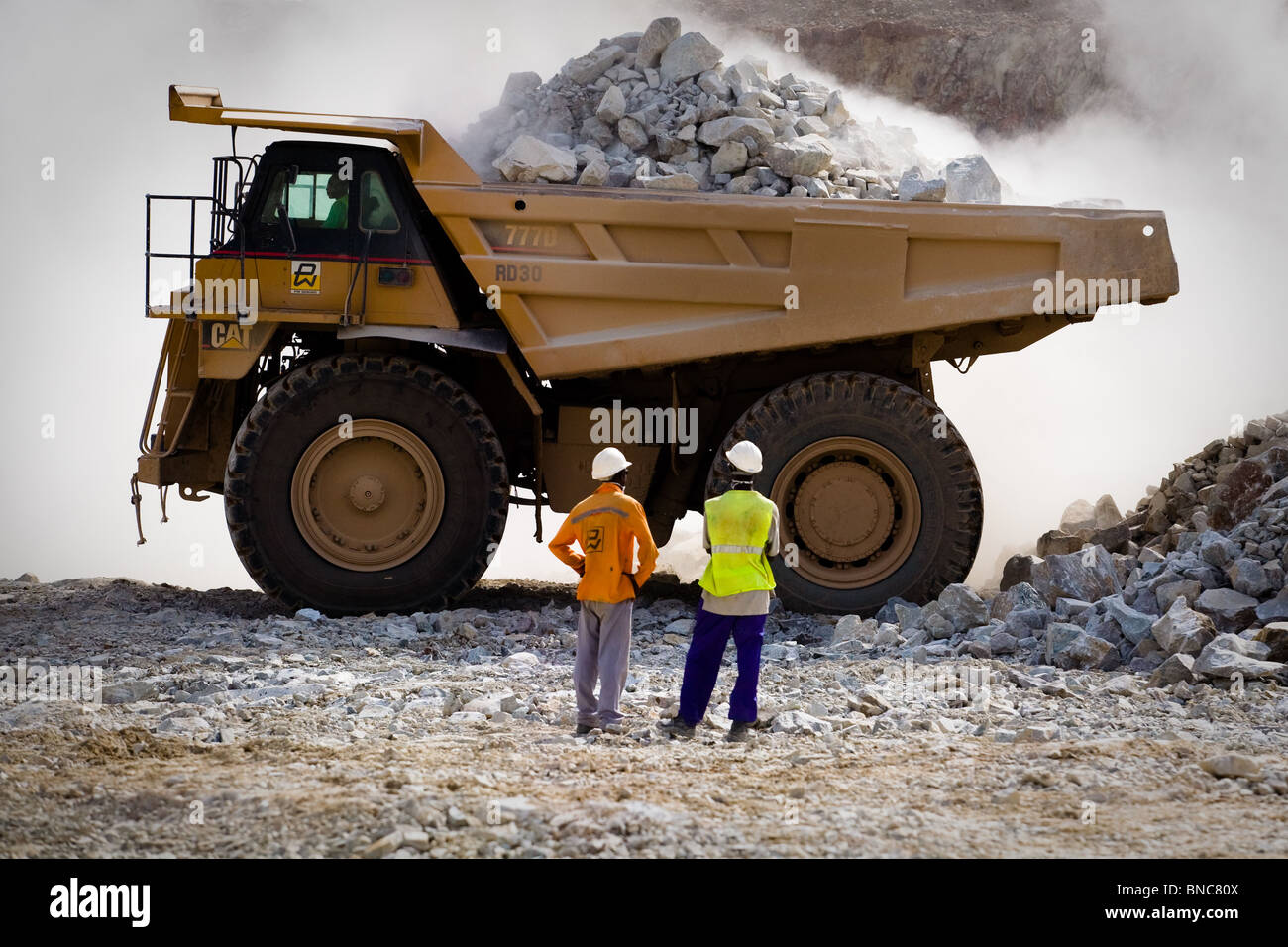 Mine workers watch as a large truck gets loaded with ore in the main pit of the Youga gold mine near the town of - Stock Image