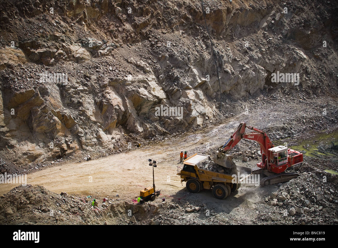 An excavator loads a large truck with ore in a pit of the Youga gold mine near the town of Youga, Burkina Faso - Stock Image
