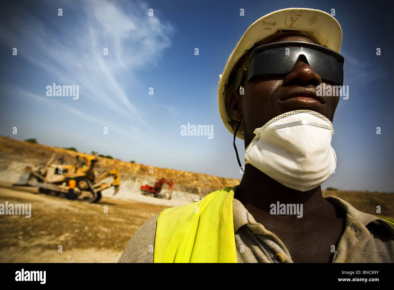 A mine worker watches over excavation operations in the main pit of the Youga gold mine - Stock Image