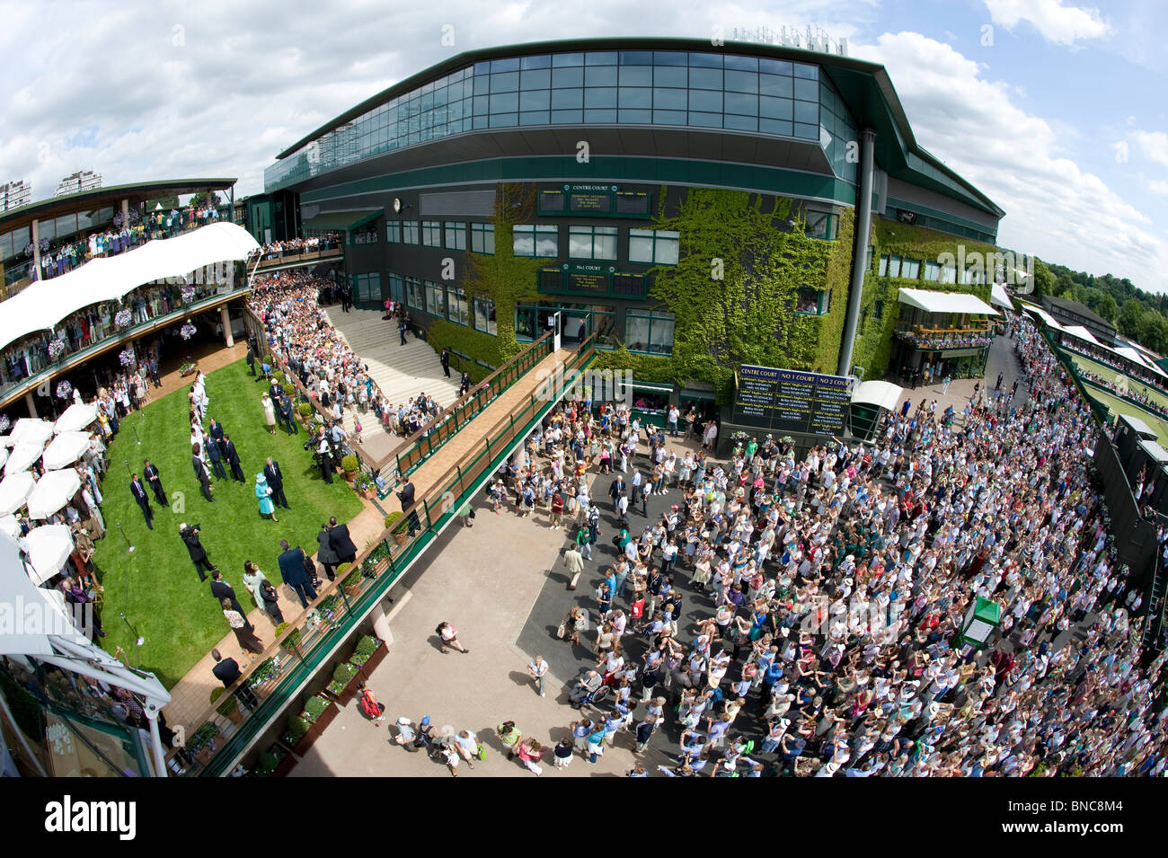 Crowds watch as HRH Queen Elizabeth II meets players on the members lawn during the Wimbledon Tennis Championships - Stock Image