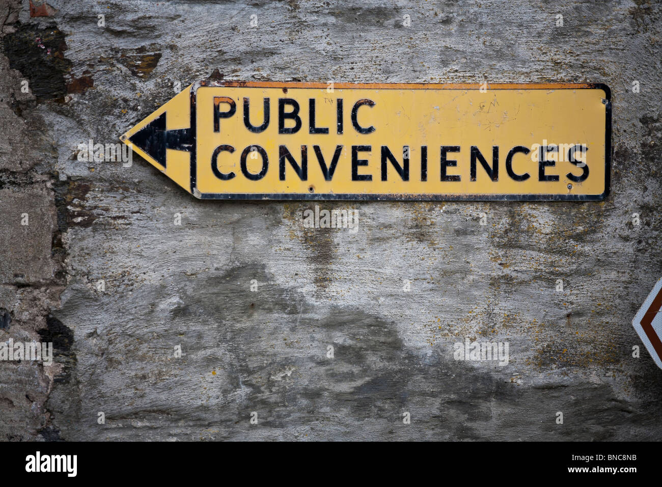 Public Conveniences Directional Sign. A yellow road sign directing people to the public toilets in Port Isaac. - Stock Image