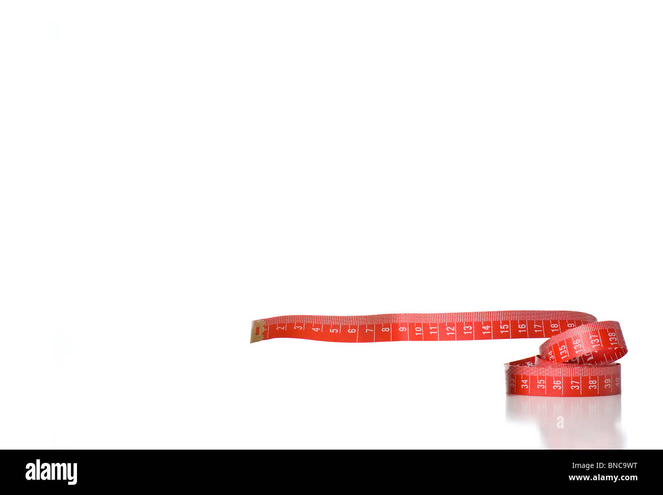 A coiled red metric measuring tape - Stock Image