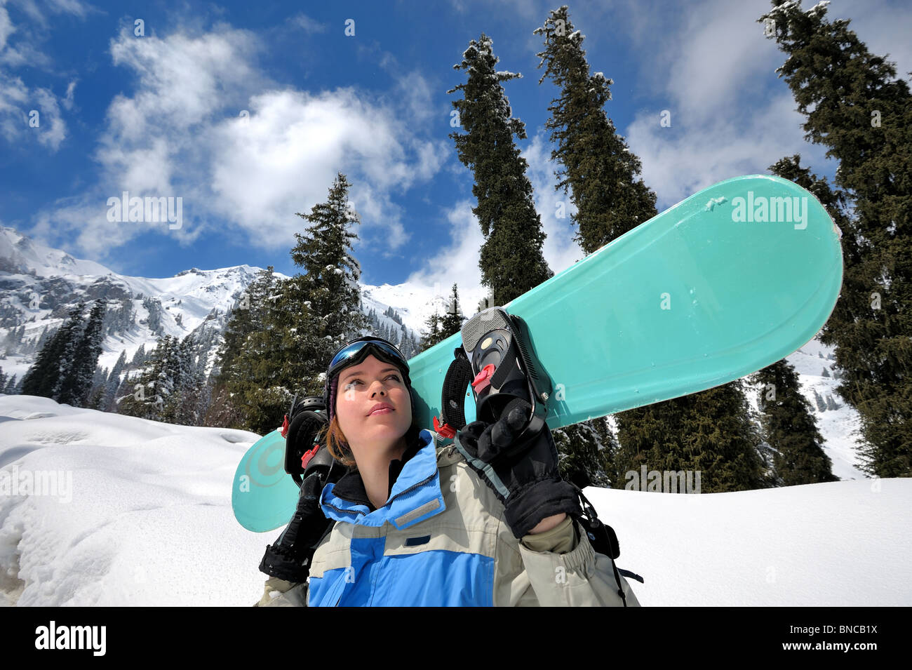 Pretty girl with snowboard looking up - Stock Image