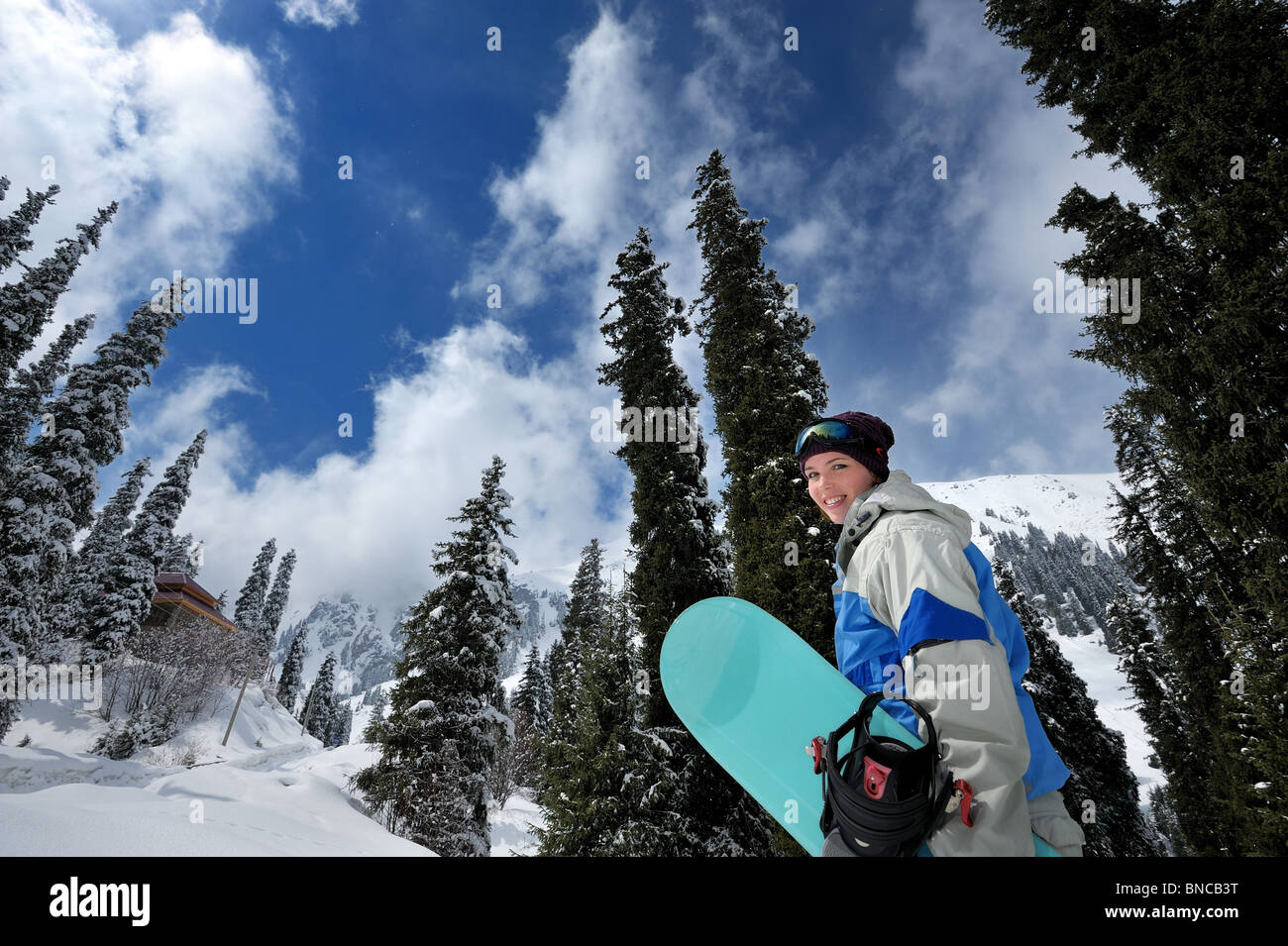 Pretty girl with snowboard smiling - Stock Image