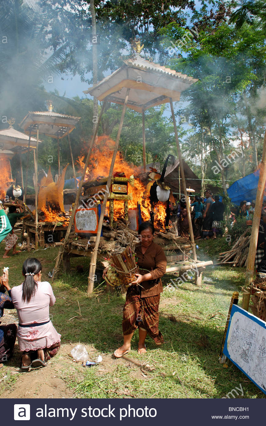 Young woman kneels and prays as coffins are burnt in Hindu mass cremation ceremony - Stock Image