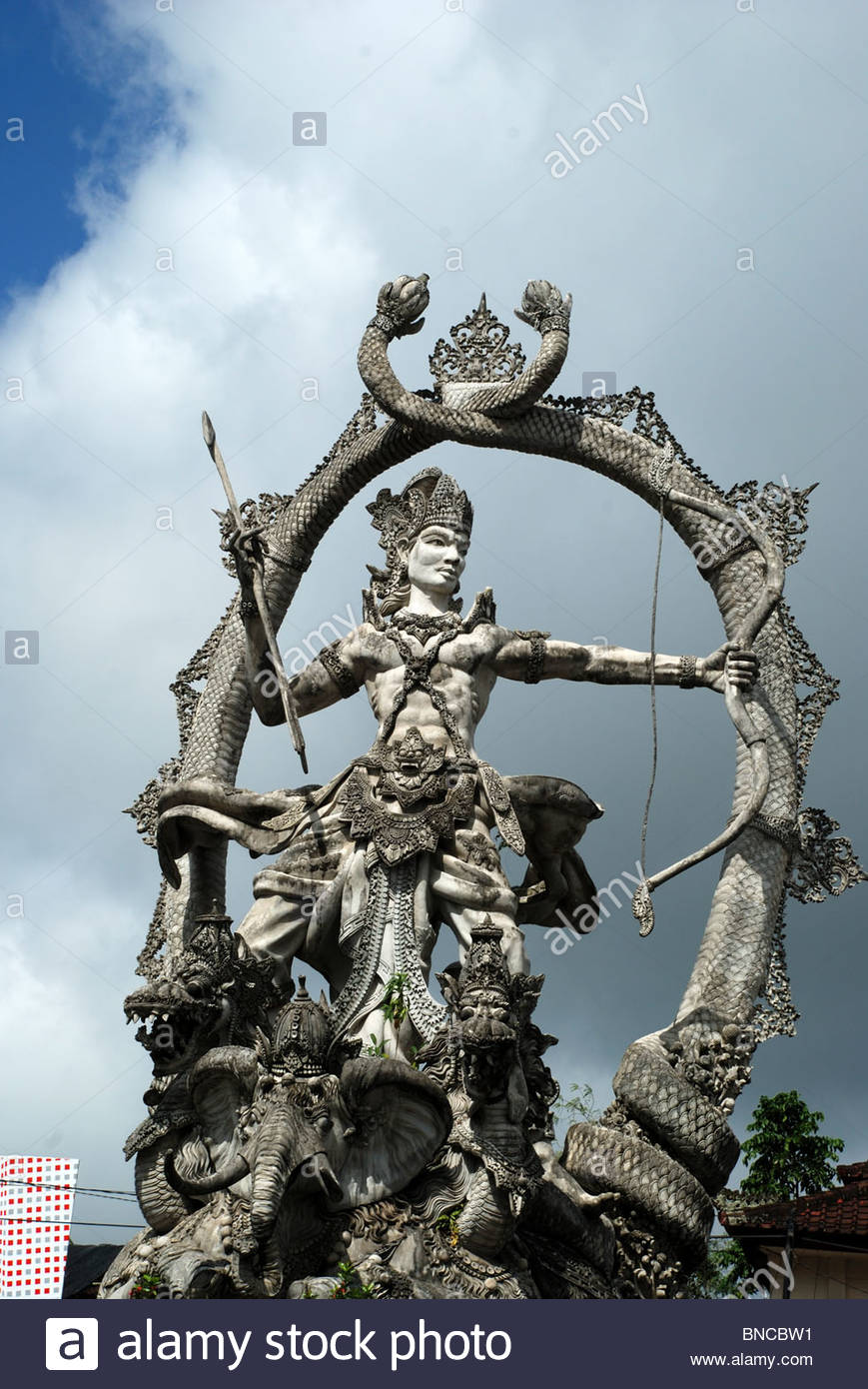 Statue of Hindu deity Arjuna holding bow and arrow and framed by serpents tails Ubud Bali Indonesia - Stock Image