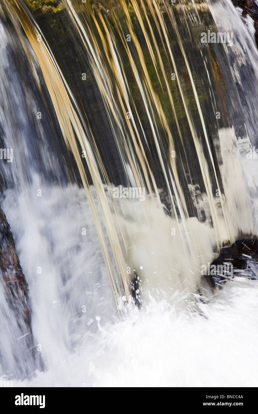 Peat staining in water as a stream goes over a weir before entering Haweswater Reservoir in the Lake district, UK. - Stock Image
