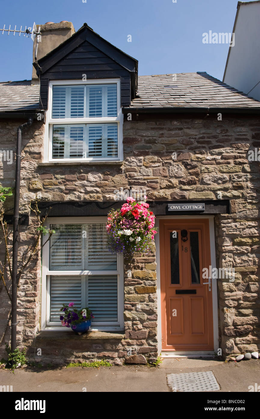 Picturesque row of terraced cottages with hanging baskets outside in Hay-on-Wye Powys Wales UK - Stock Image
