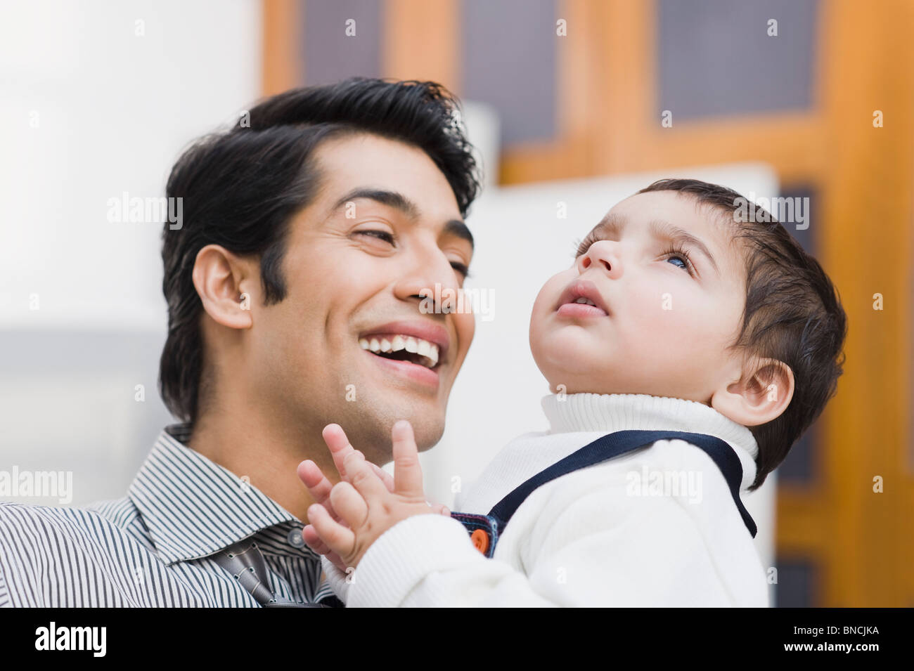 Man carrying his son and smiling - Stock Image