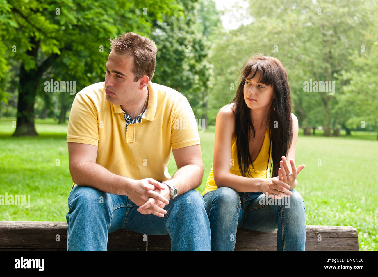 Young couple sitting outdoors on bench having relationship problems - Stock Image