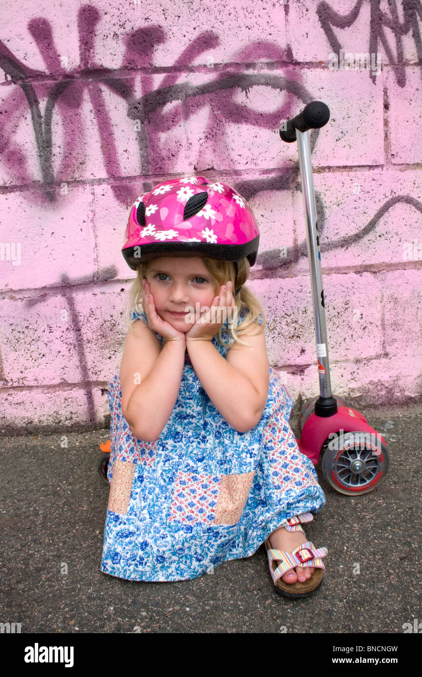 Young girl sat on her scooter feeling a bit sad - Stock Image