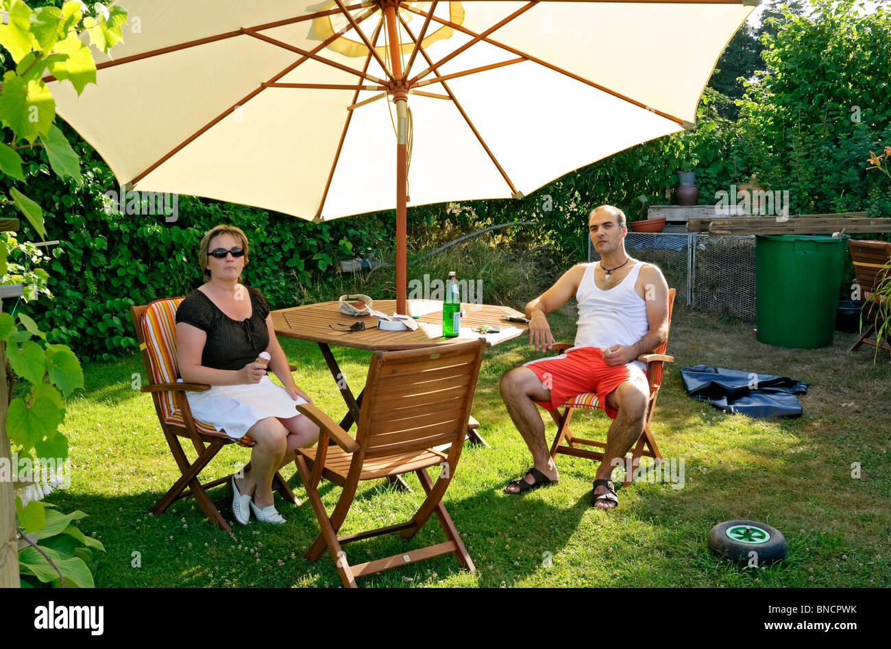 Man & woman 30s relaxing under parasol in garden. - Stock Image