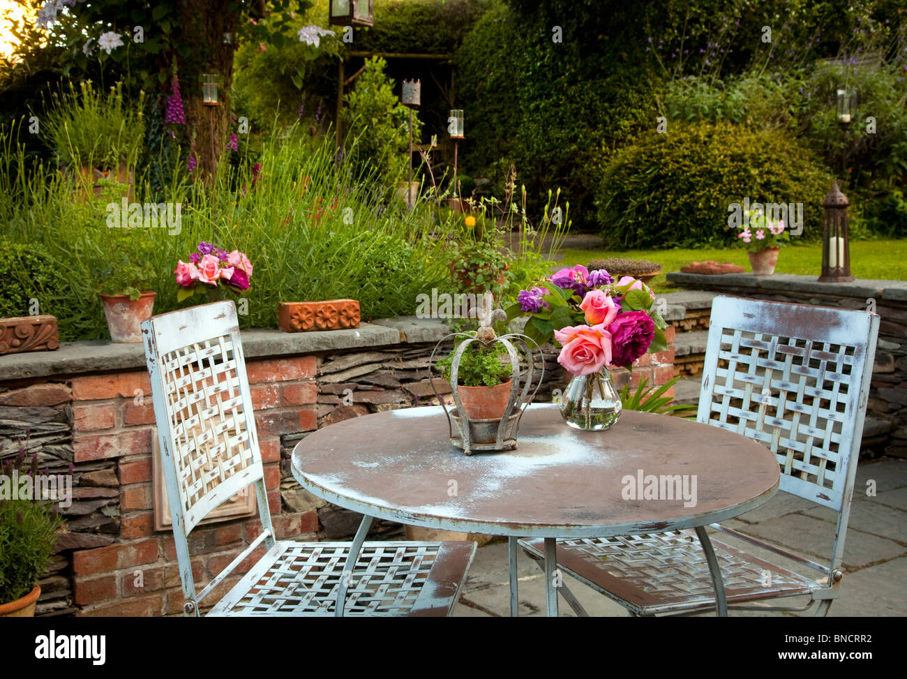 Metal table and chairs on patio with candles and lanterns in garden at night - Stock Image