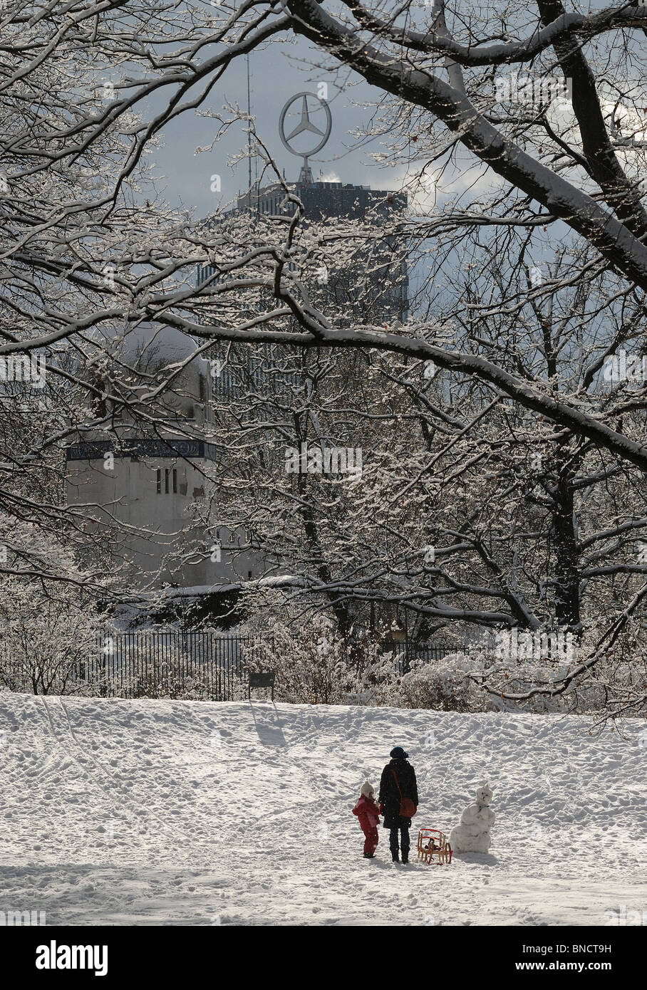 Woman, child and snowman in the snowy Grosser Tiergarten in front of  of the Berlin zoo and the Europa Center, Berlin, - Stock Image