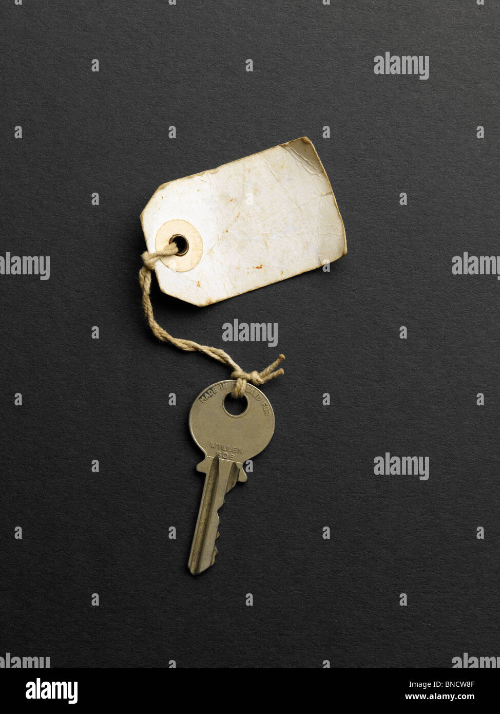 Old key with label no writing - Stock Image