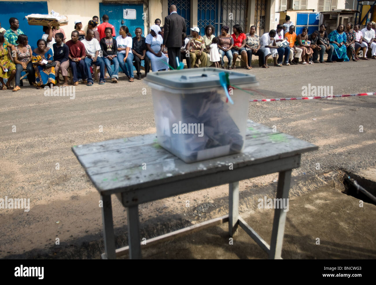 People sit on a bench in the street as they wait to vote at a polling station in  capital Accra during presidential - Stock Image