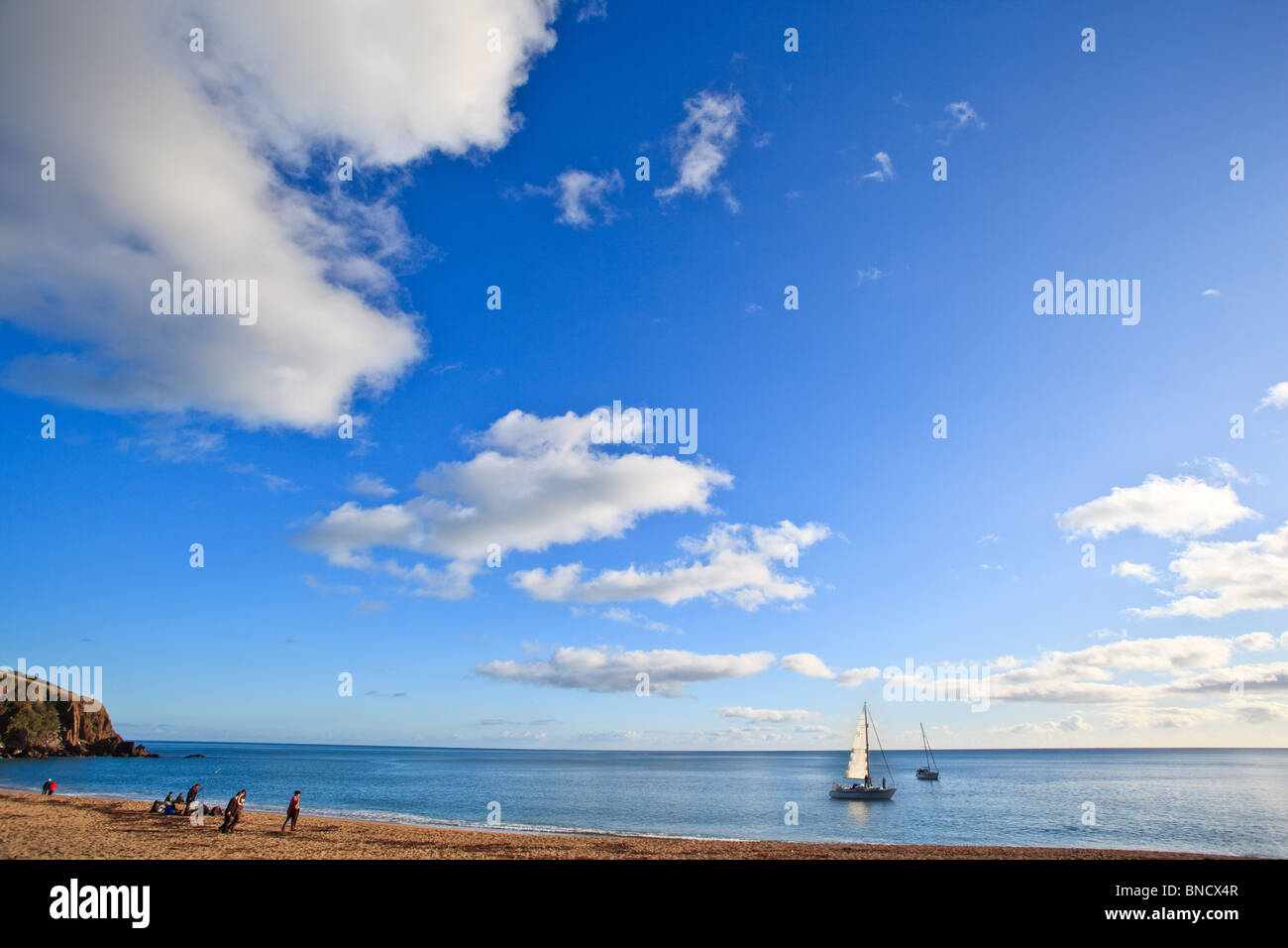 Blackpool Sands Devon beach scene with small yacht on sea with blue sky and white clouds - Stock Image