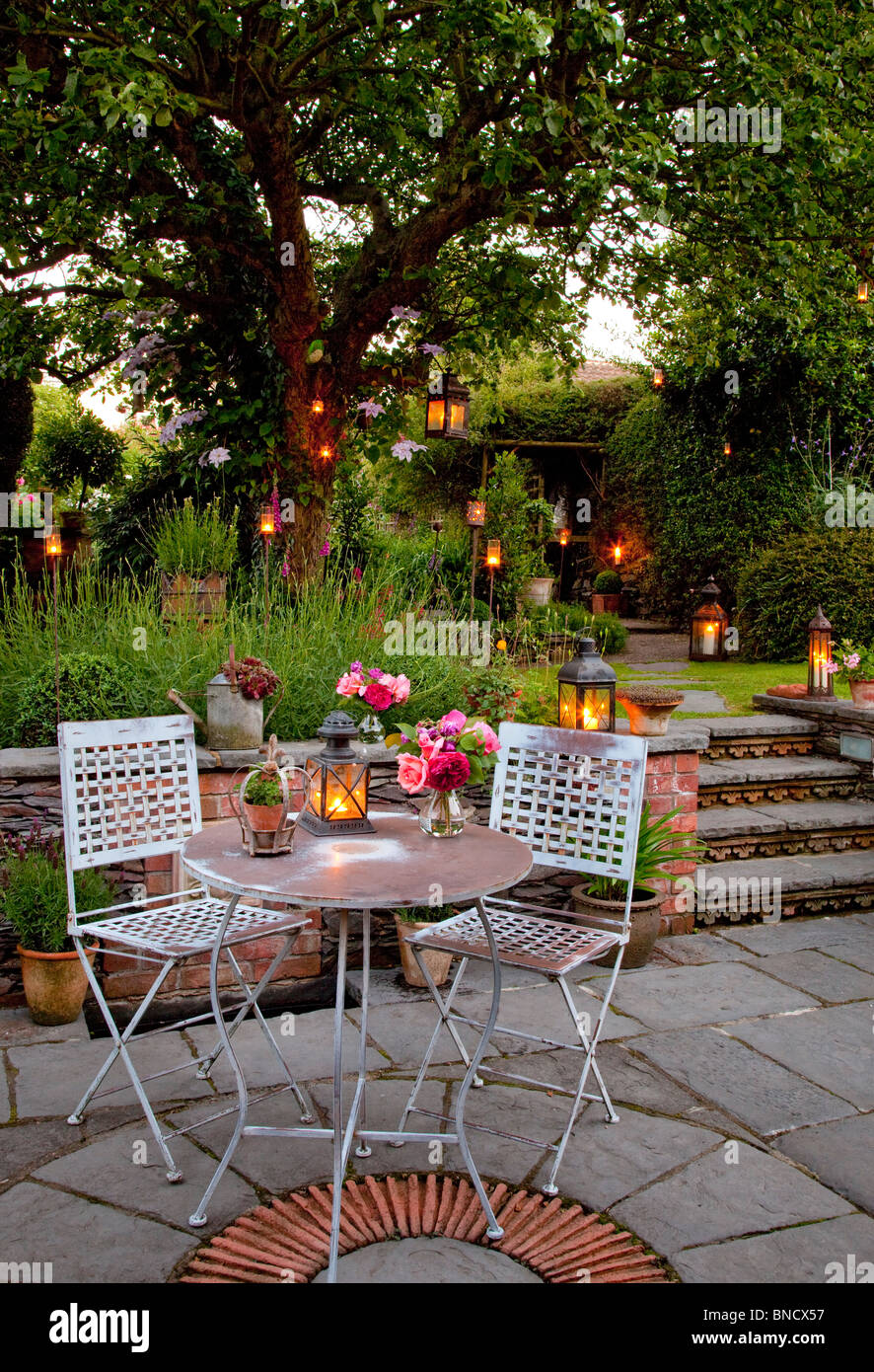 Metal table and chairs on patio with candles and lanterns in