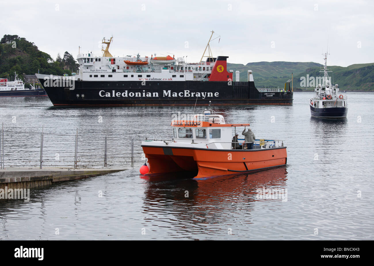 A ferry entering Oban with two smaller boats in front Stock Photo