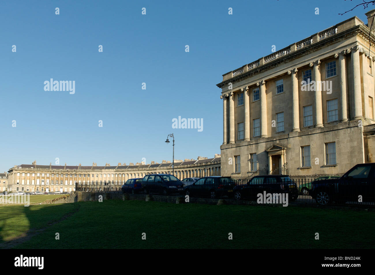 Classically inspired columned Royal crescent in Bath in the morning with a blue sky and cars parked along the street. - Stock Image