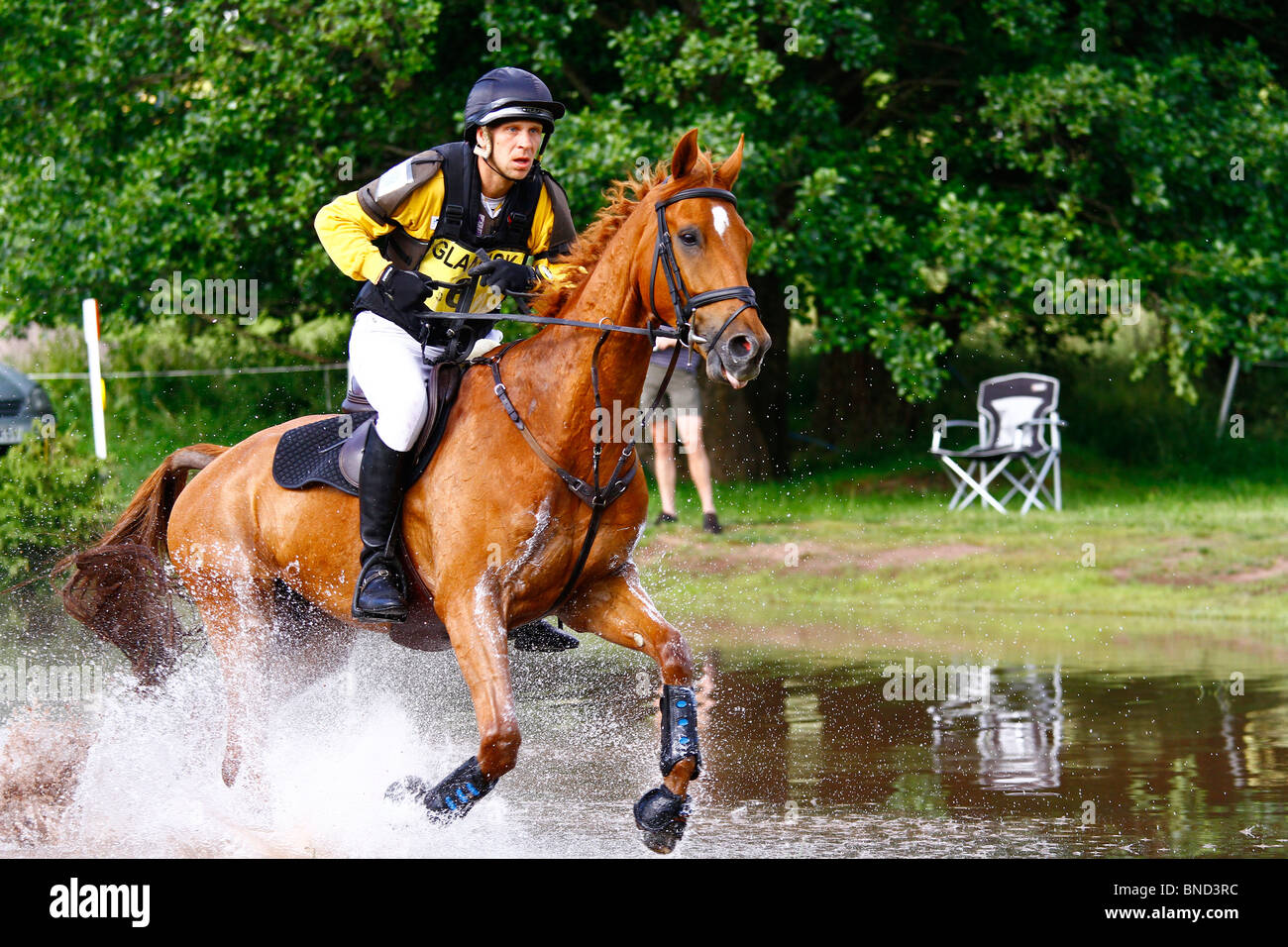 Eventing - Horse and rider galloping through water at Glanusk Horse Trials in Wales. - Stock Image