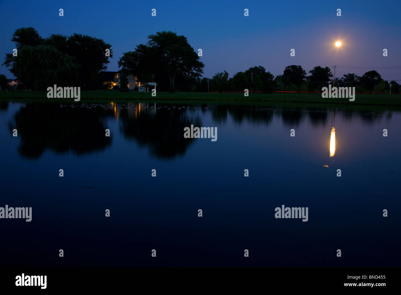 Rising moon over the lake - Stock Image