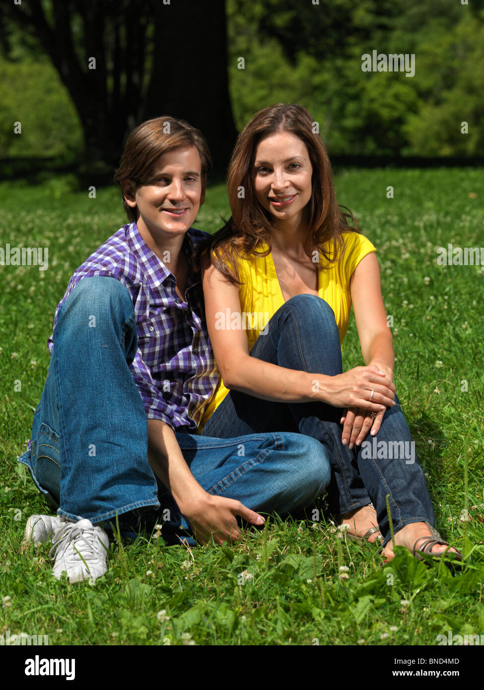 Young happy smiling couple in their early thirties sitting on grass in a park Stock Photo