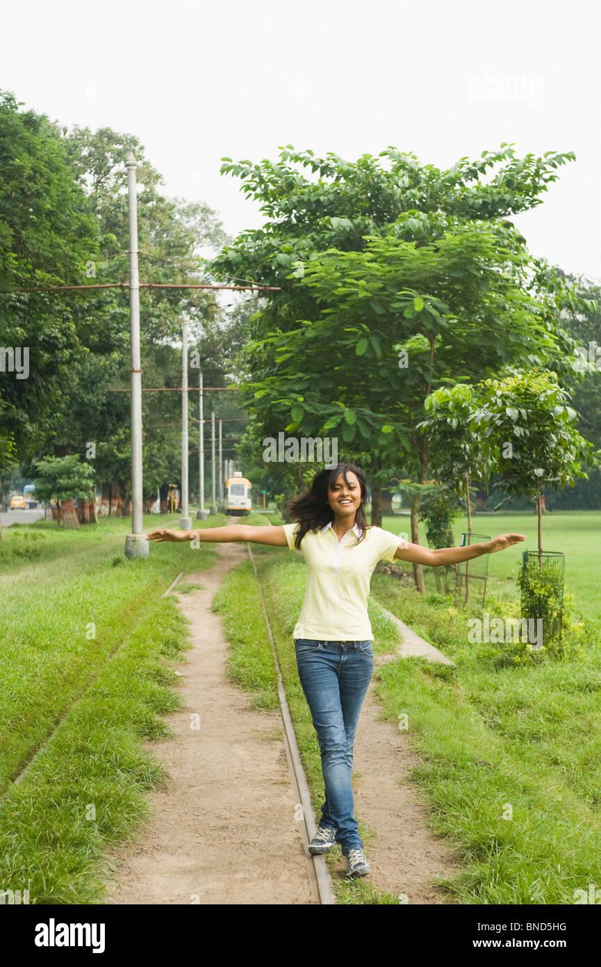 Woman walking on a railroad track, Kolkata, West Bengal, India - Stock Image