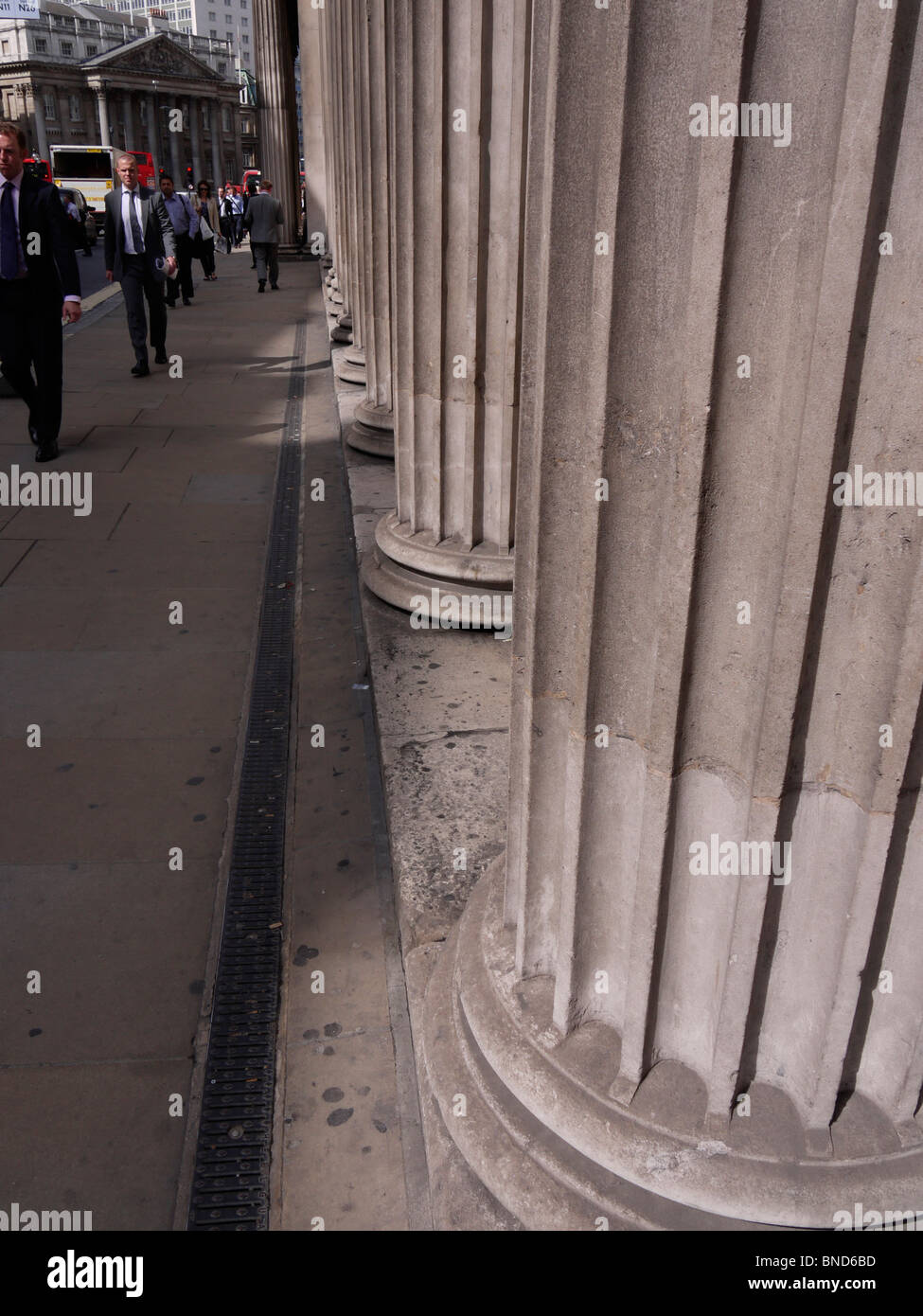 bank of england pillars with commuters walking past, london - Stock Image