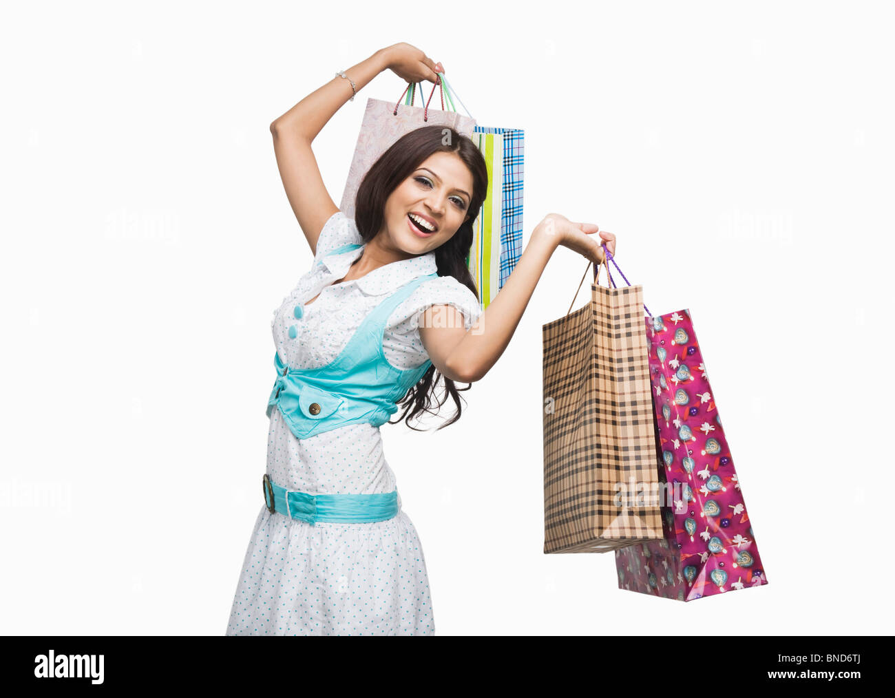 Woman carrying shopping bags and smiling - Stock Image