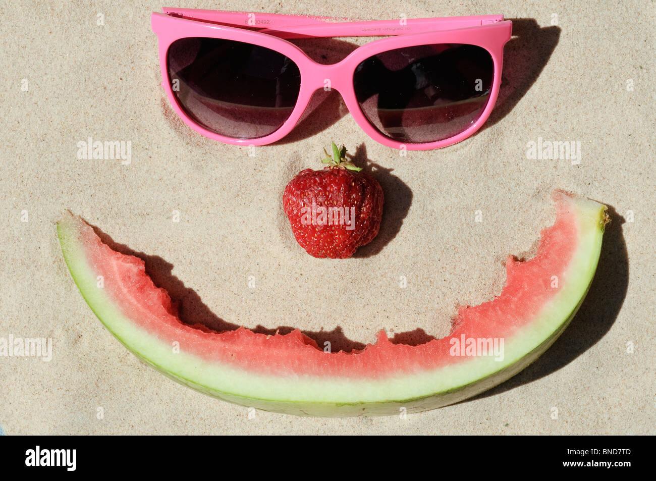 Symbolic happy summer face on a sunny sandy beach - Stock Image