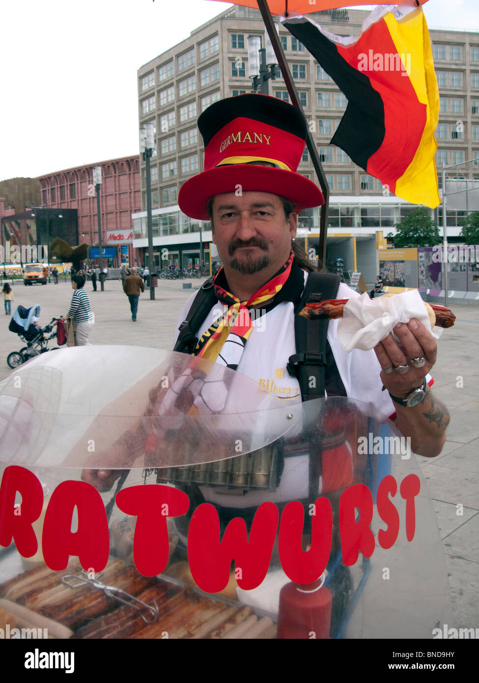 Man selling traditional Bratwurst sausage hot dogs from mobile stall in Berlin Germany Stock Photo