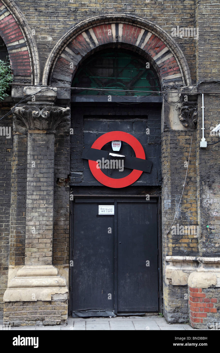 Ornamented brick arch and secure black door in railway arches along Crucifix Street, London - Stock Image