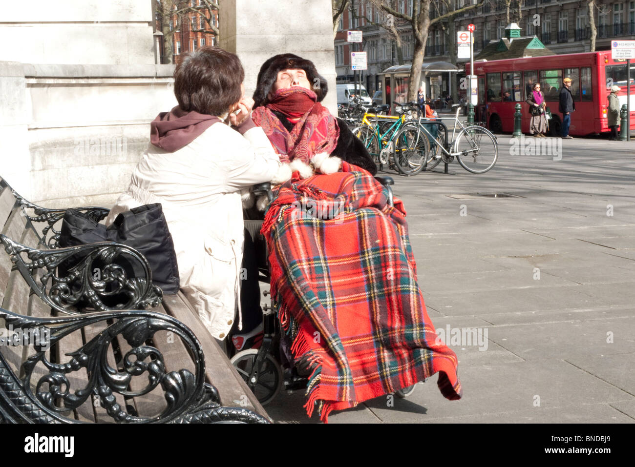 An elderly woman in a tartan blanket and wheelchair accompanied by her minder outside the V & A Museum London - Stock Image