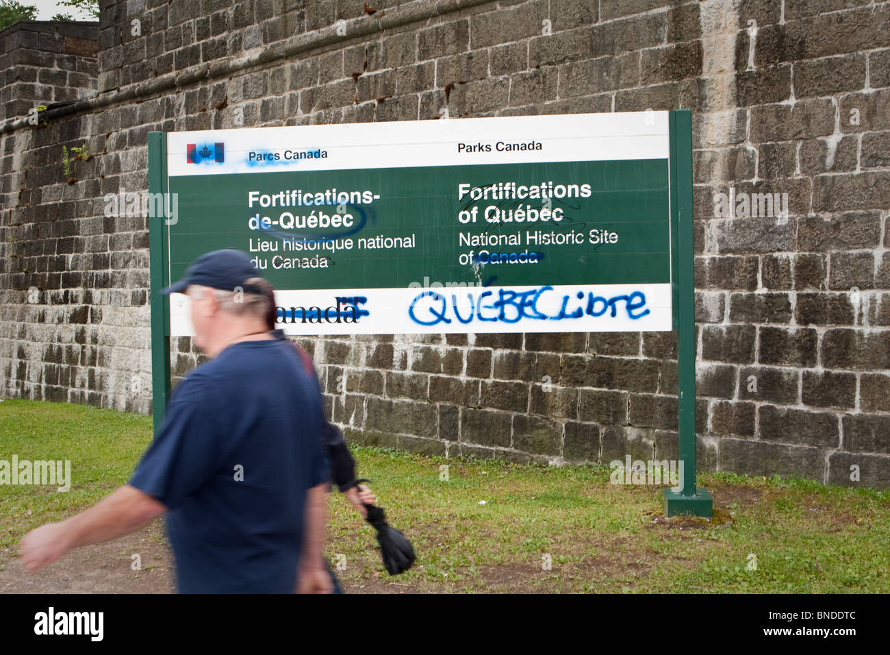 2 persons walk by a board vandalized by Quebec separatists in Quebec City - Stock Image