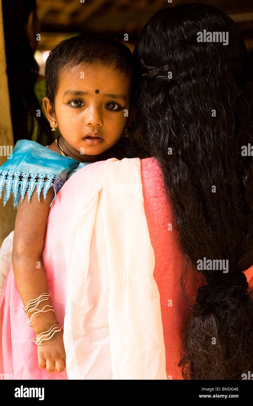 A baby wearing bangles and eye make up looks into the camera in Kerala, India. Her mother carries the baby on her - Stock Image