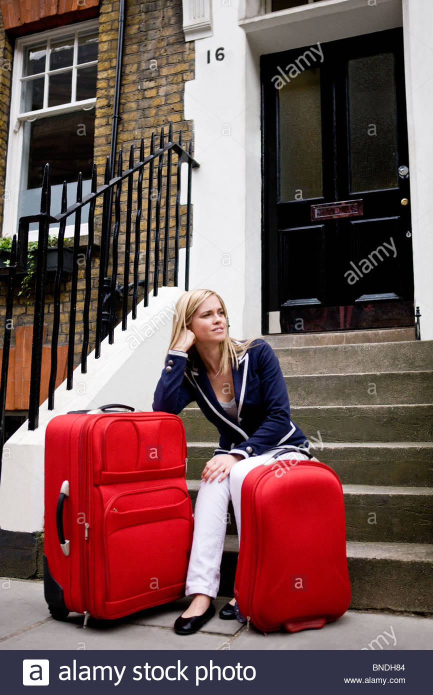 A young woman waiting on her doorstep with her suitcases - Stock Image