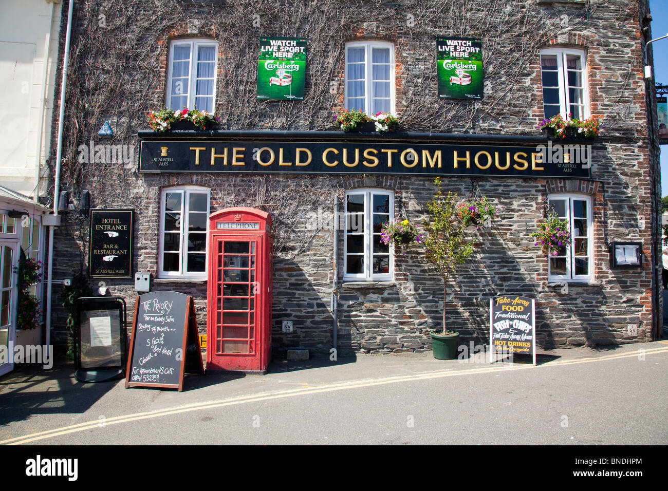 The old custom house in Padstow, Cornwall, England. Old style pub with red telephone box outside Stock Photo